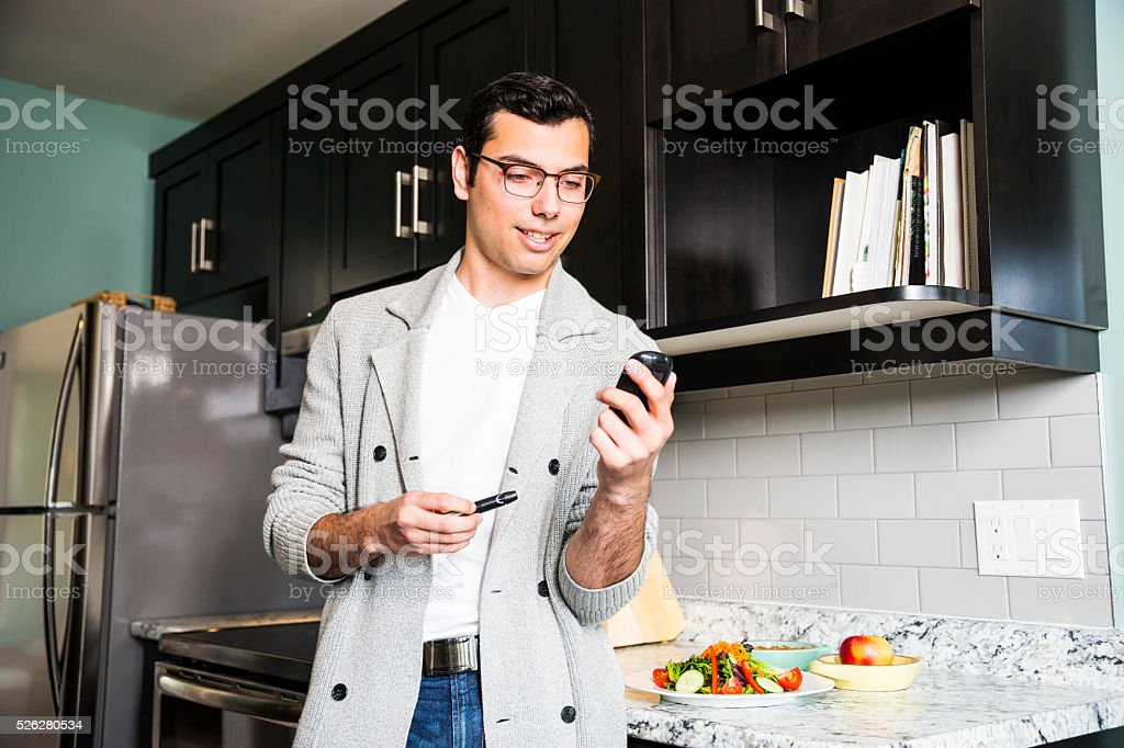 Latino man monitoring his diabetes. stock photo