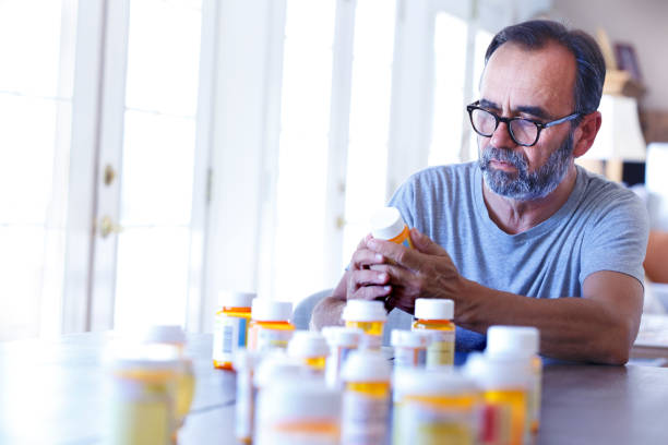 Latino Man Sitting At Table Sorting Through Prescrption Medications A latino baby boomer sits at his dining room table and sorts through various prescription medications as sunlight filters in through the window behind him bathing the room with a soft glow of light. pill container stock pictures, royalty-free photos & images