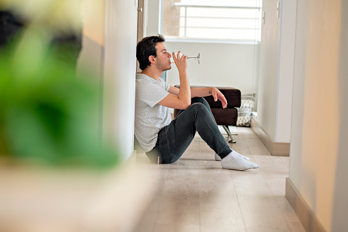 25-year-old Latino male is dressed casually sitting in the hallway of his bed room having a glass of wine while enjoying the moment alone