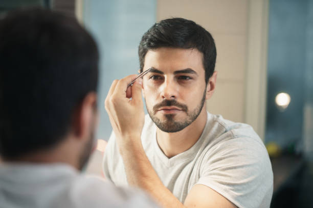 Latino Man Trimming Eyebrow For Body Care In Bathroom stock photo