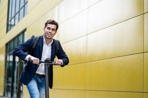 Average 25-year-old formally dressed Latino man uses his electric skateboard for transportation around town
