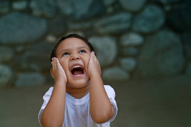 Latino preschooler overwhelmed with happiness holds his face with both hands and screams really loud. stock photo