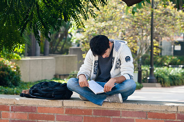 """Latino University Student Studying Between Classes On Campus """"Los Angeles, USA - October 24, 2011: A young Hispanic boy studies on campus at UCLA on October 24, 2011 as part of his educational development for the future. The cost of higher education in America is of significant concern for lower income students."""" ucla medical center stock pictures, royalty-free photos & images"""