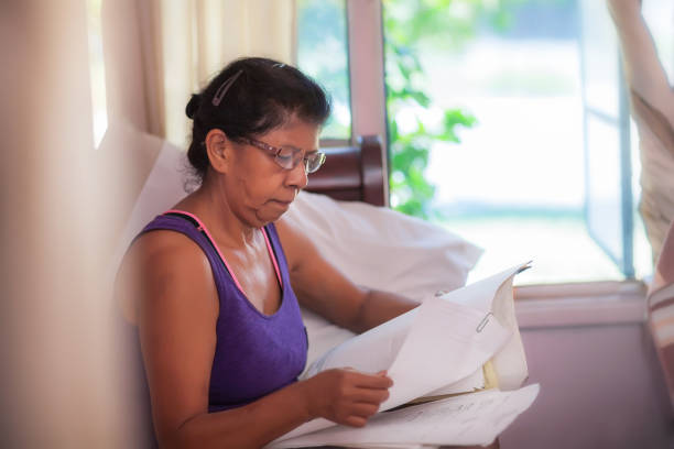 Latino woman comparing monthly mortgage statements, considering mortgage relief assistance or refinancing. stock photo