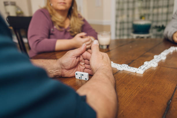 latinx family and friends playing dominoes stock photo