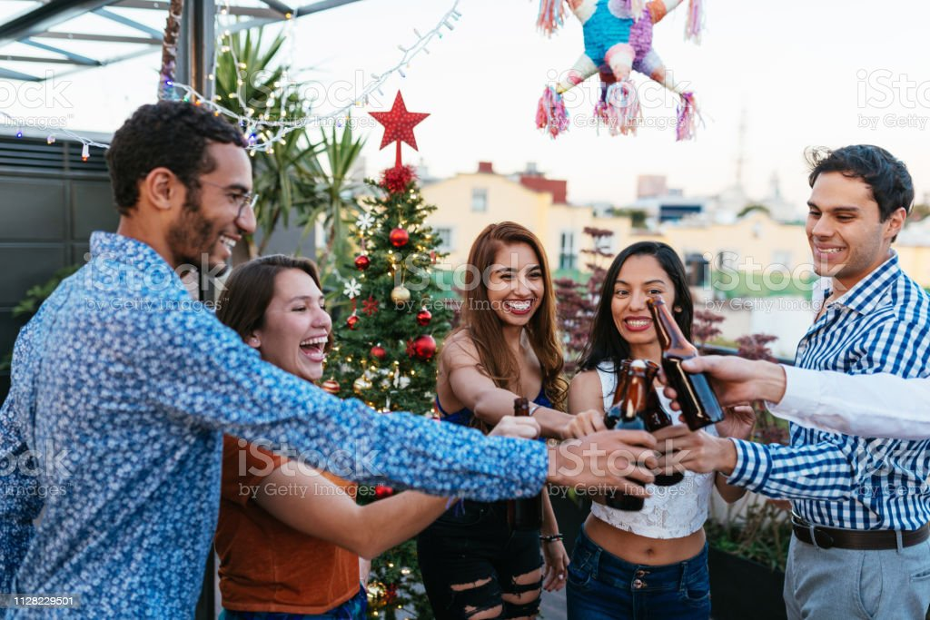 The Rooftop Christmas Tree.Latinx Friends Drinking Beer And Celebrating Christmas On