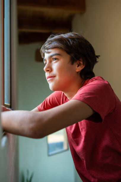 latinx preadolescent boy looking through window hopefully, reflecting A latino, hispanic preadolescent boy looking through window, reflecting, hopeful, serene boy looking out window stock pictures, royalty-free photos & images
