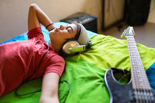 Latinx pre-teen boy listening to music calmly in his bedroom