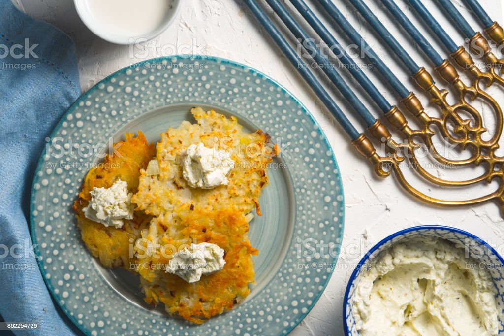 Latkes and curd cheese on a plate and on a blue napkin, chanukia stock photo