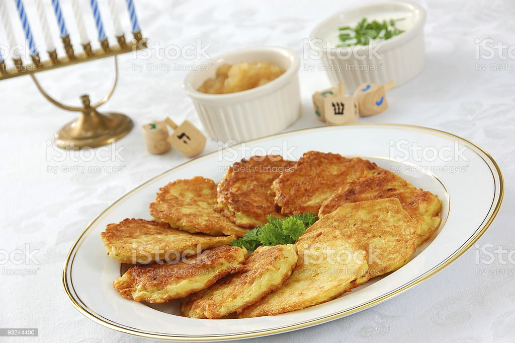 Latkes for Hanukkah A table set for Hanukkah, with dreidels, menorah, and a plate of crispy latkes (potato pancakes) served with apple sauce and sour cream. Apple Sauce Stock Photo