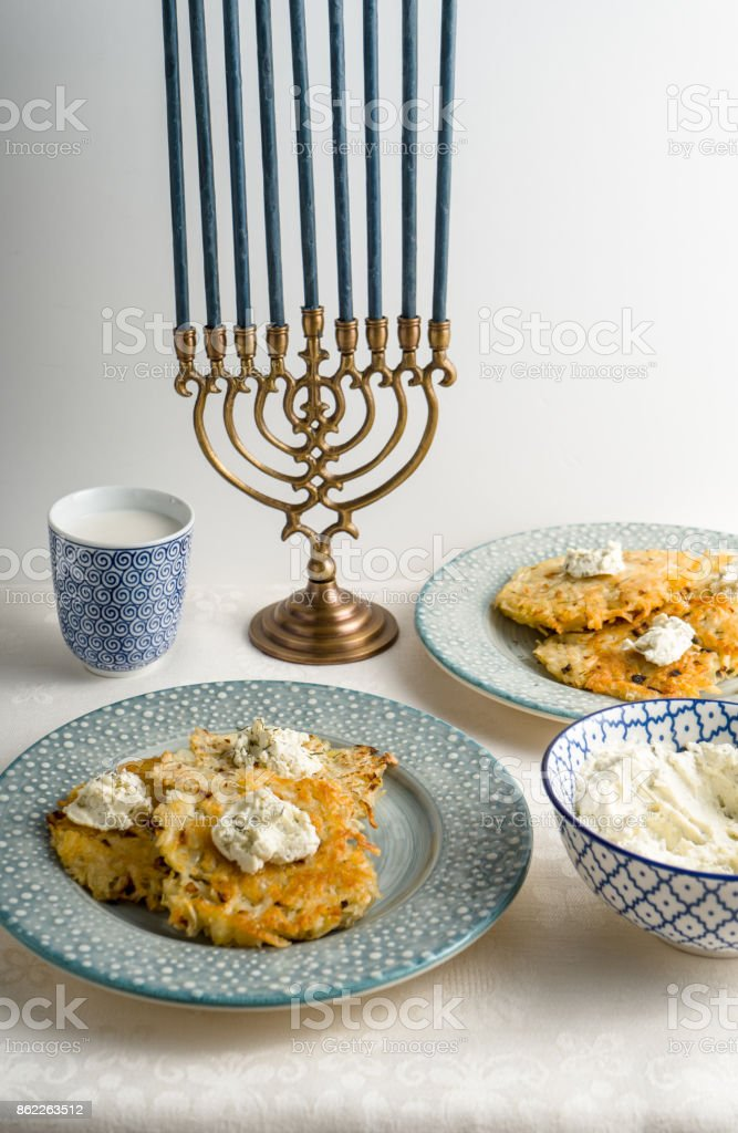 Latkes on a plate, Hanukkah, cups with milk on a white tablecloth side view stock photo