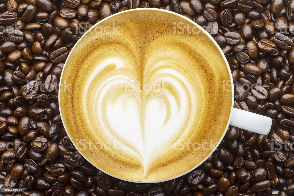 Latte art, coffee in beans background royalty-free stock photo