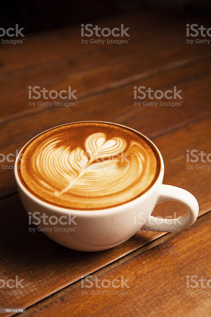 Latte art, coffee on the wooden desk as background. royalty-free stock photo