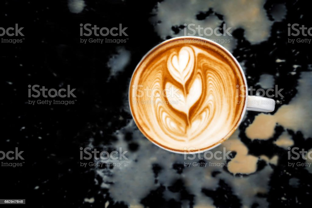 Latte art of two heart in white cup. Dirty spill coffee on black background. Top view. foto de stock libre de derechos