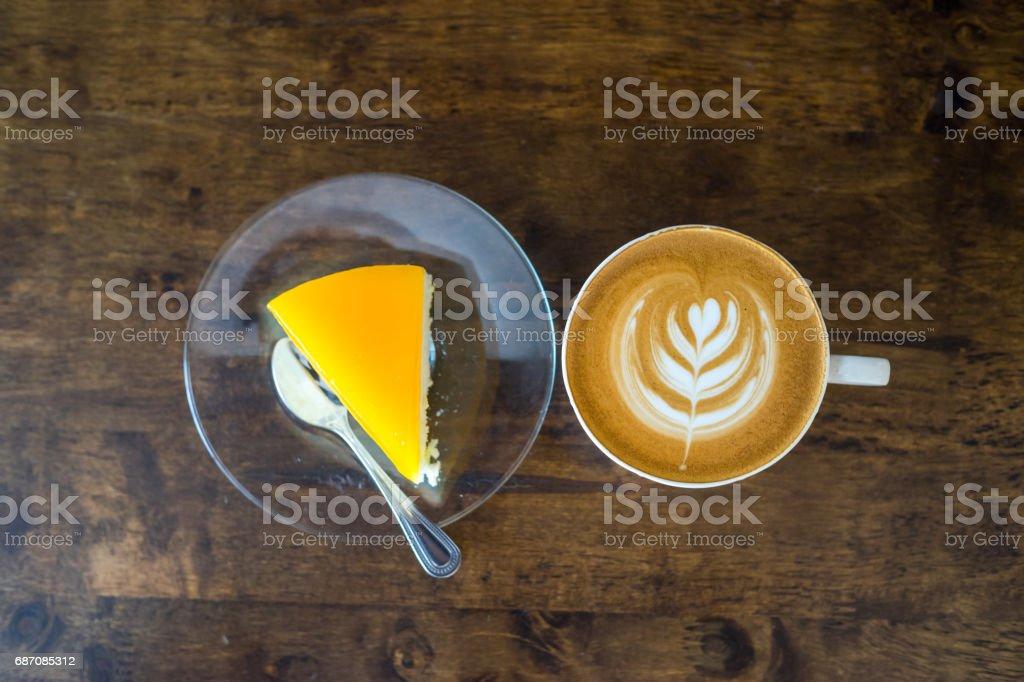 latte art with orange cake on wood table. Lizenzfreies stock-foto