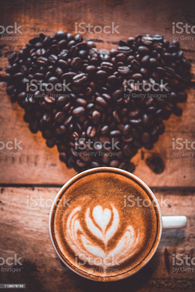 Latte arts coffe. White cup of hot coffee on wooden table. Cafe with...