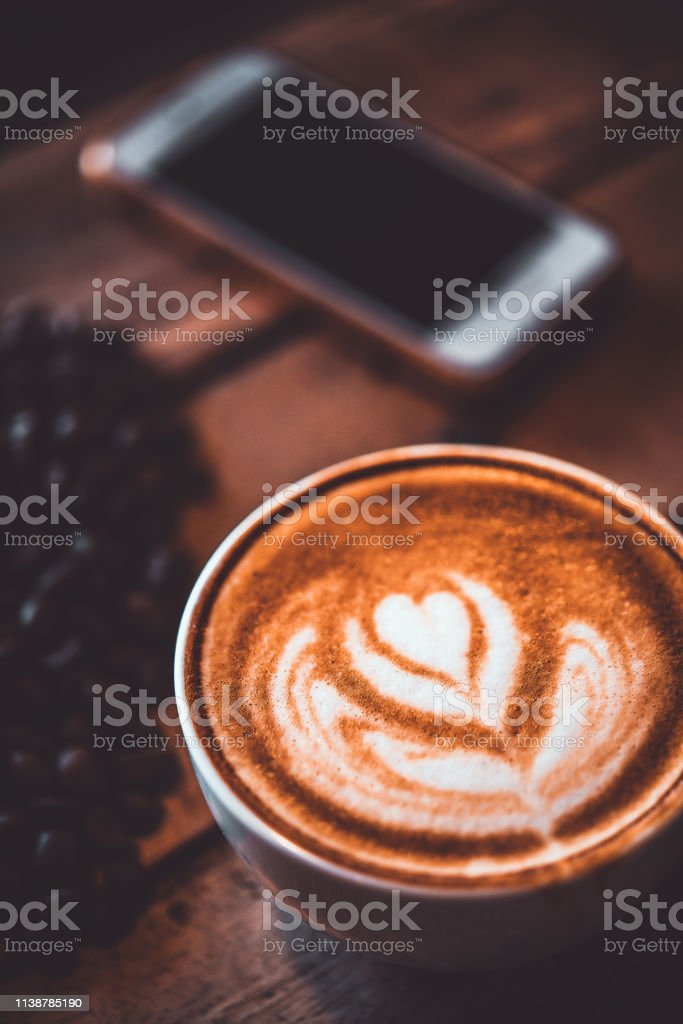 Latte arts coffe. White cup of hot coffee on wooden table with heart...