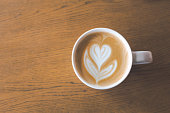 Latte coffee art in white cup on wooden background
