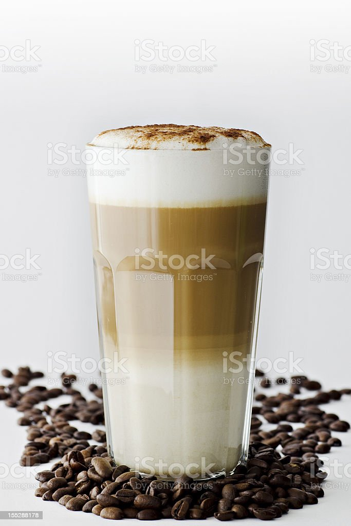 A latte macchiato in coffee beans on white backdrop royalty-free stock photo