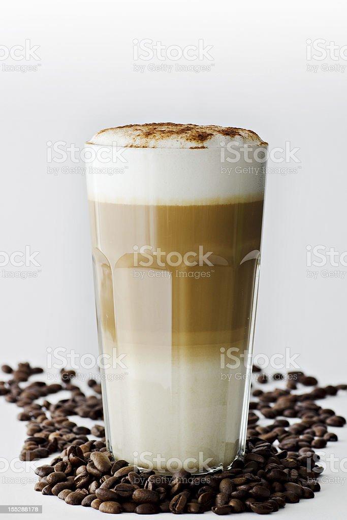 A latte macchiato in coffee beans on white backdrop stock photo