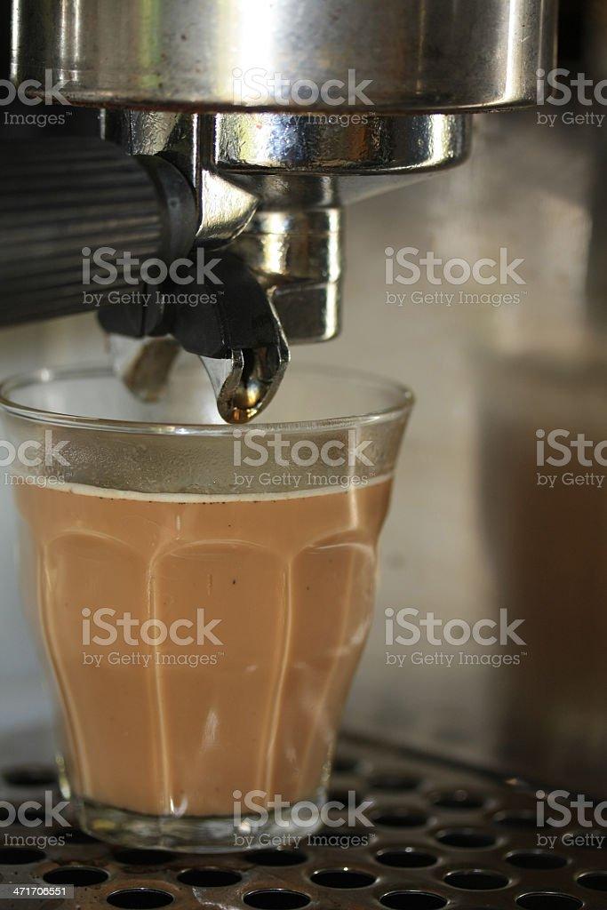 Latte macchiato under an espresso maker royalty-free stock photo