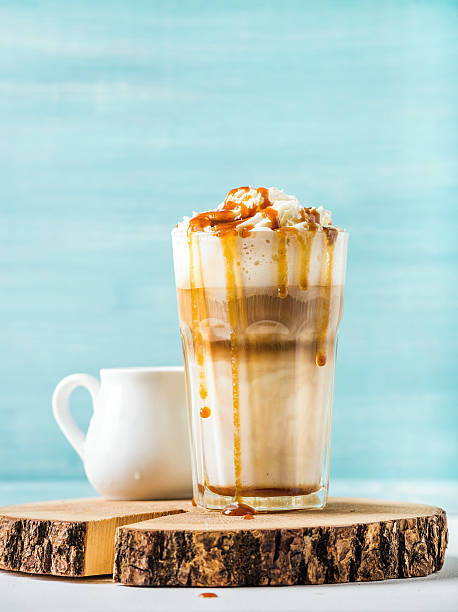 latte macchiato with whipped cream and caramel sauce in tall - mocca stock-fotos und bilder