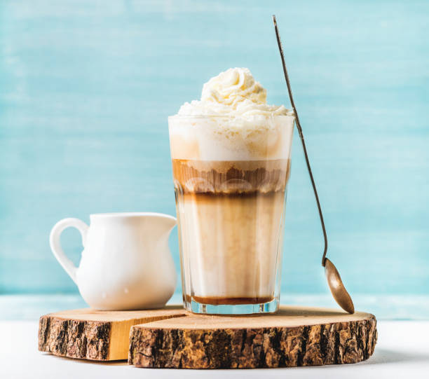 Latte macchiato with whipped cream, serving silver spoon and pitcher on wooden round board over blue painted wall background stock photo