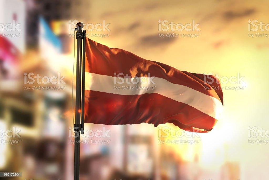 Latvia Flag Against City Blurred Background At Sunrise Backlight stock photo