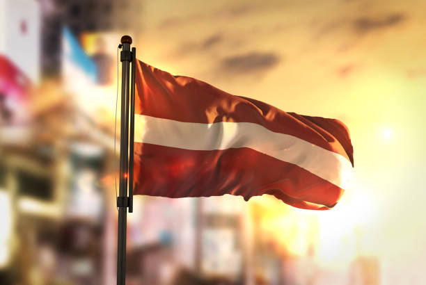 Latvia Flag Against City Blurred Background At Sunrise Backlight stock photo