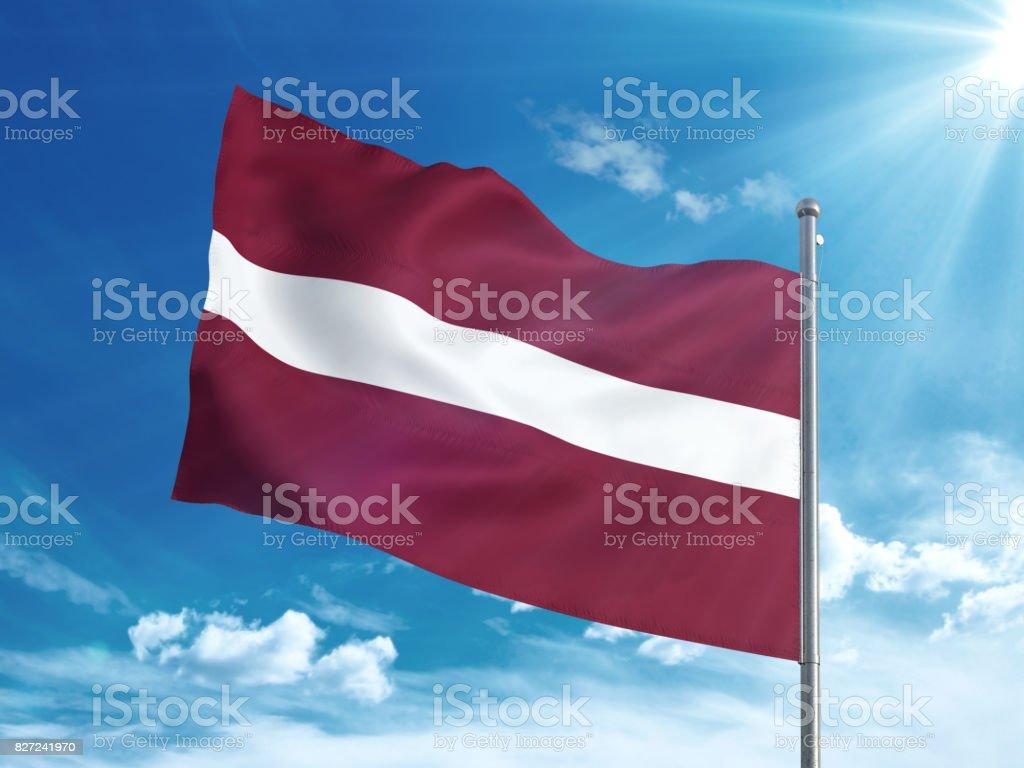 Latvia flag waving in the blue sky stock photo