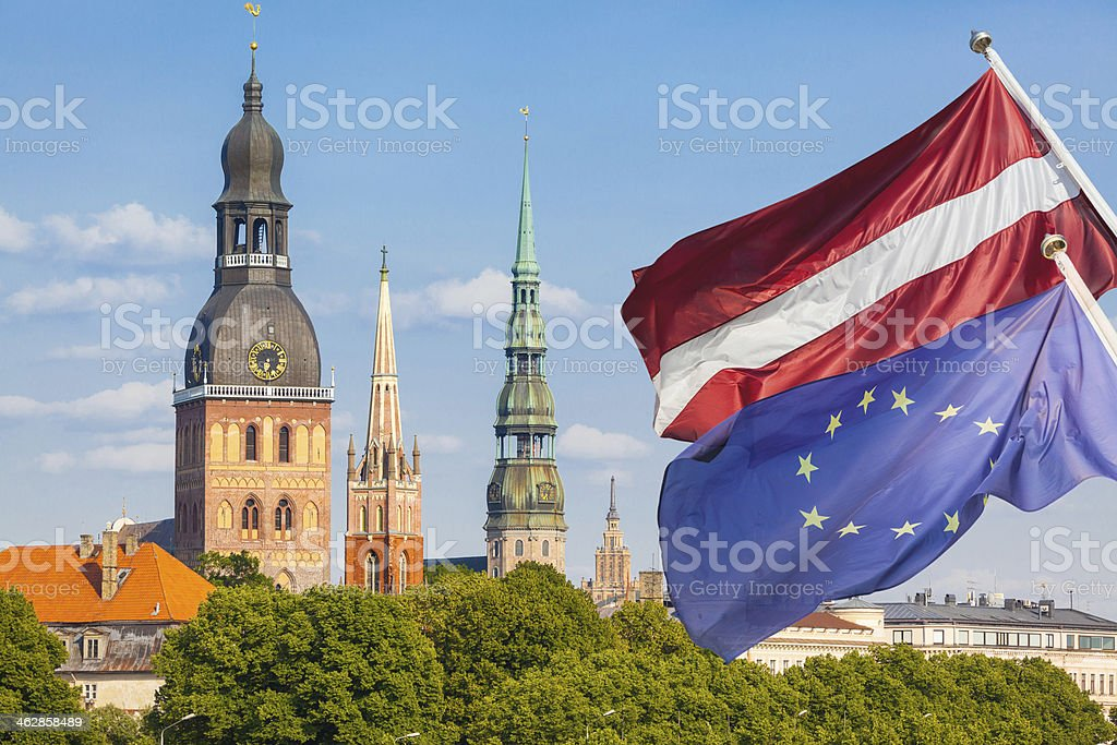Latvian and European Flags with Riga Cityscape on Background stock photo