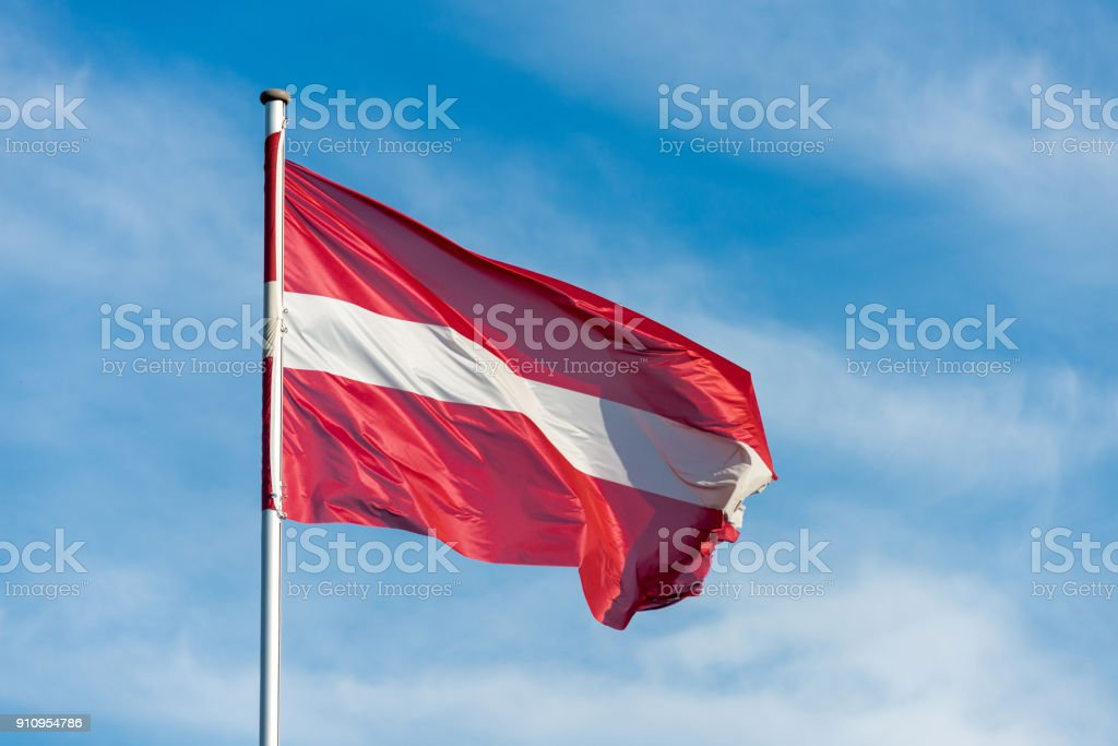 Latvian flag waggling in the wind with sky in background stock photo