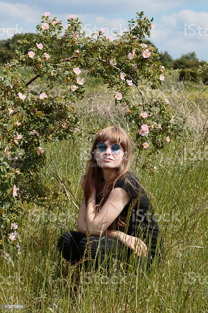 Crouching Latvian outdoor girl with dog rose bush in meadow stock photo