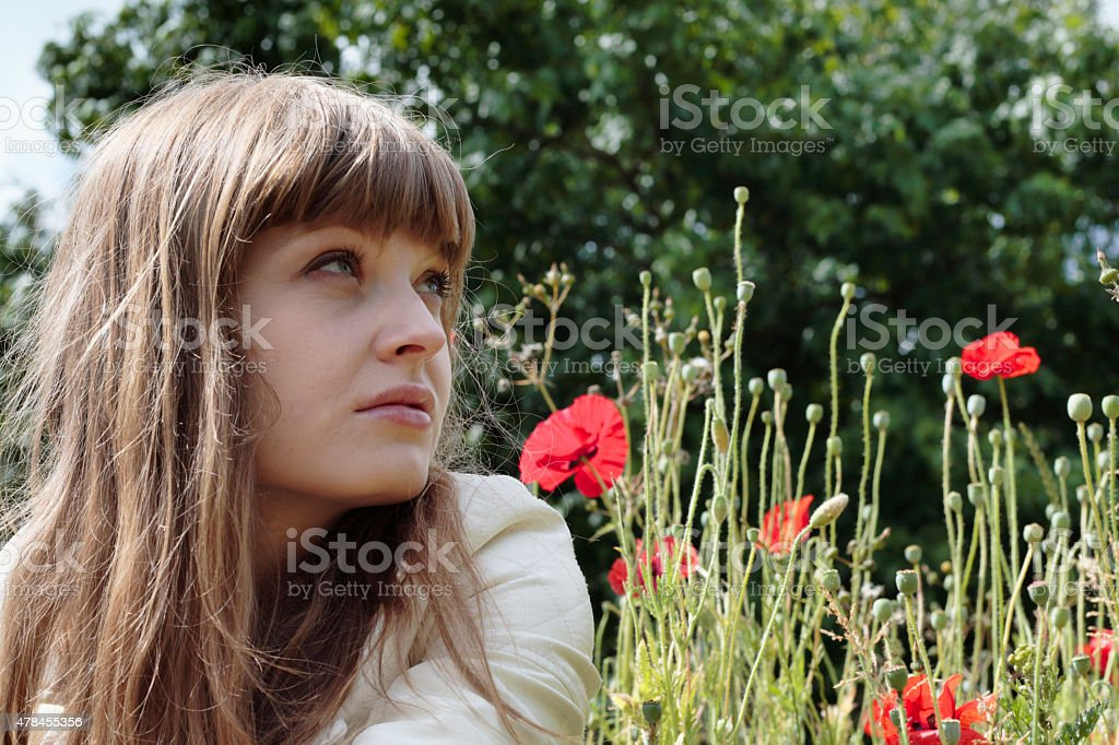 Latvian flower girl outdoors profile with red poppies stock photo
