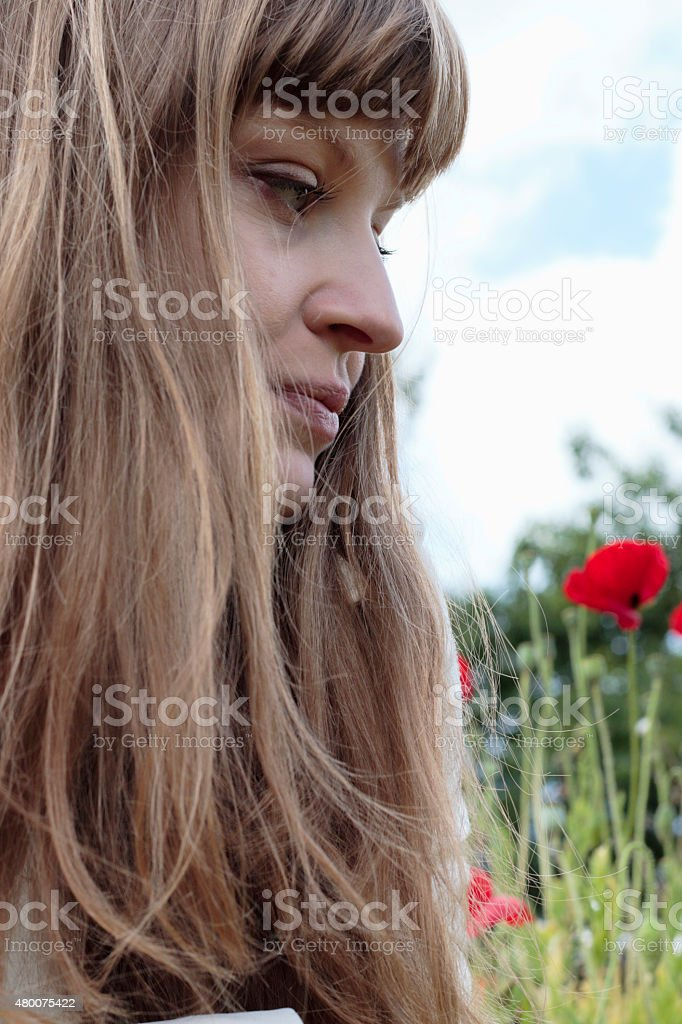 Long-haried Latvian flower girl outdoors profile with red poppies stock photo