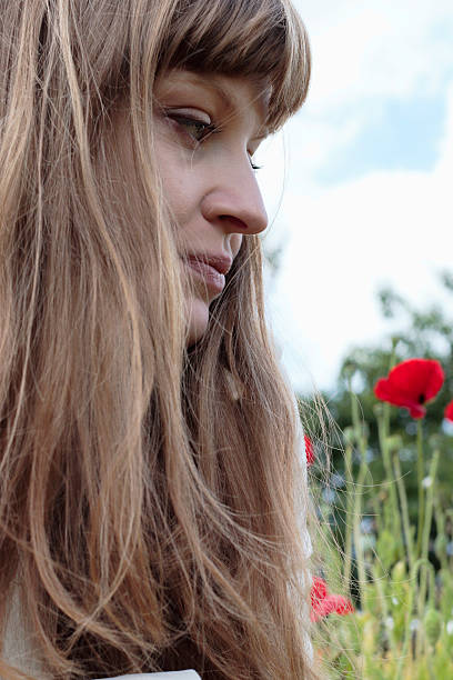 long-haried latvian flower girl outdoors profile with red poppies - whiteway latvian outdoor girl stock photos and pictures
