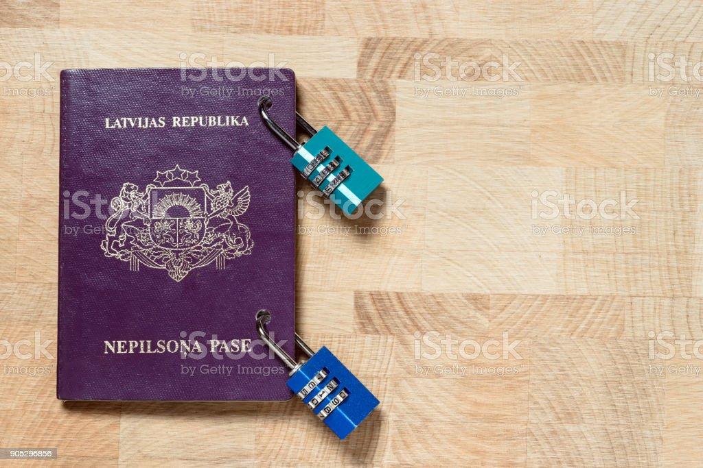 Latvian non-citizen purple passport locked with combination locks, concept, The words 'LATVIJAS REPUBLIKA', 'NEPILSONA PASE' (Latvian) meaning Republic of Latvia, Alien's passport. stock photo