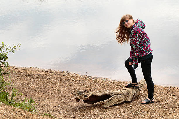 latvian outdoor girl triumphs over driftwood crocodile - whiteway latvian outdoor girl stock photos and pictures