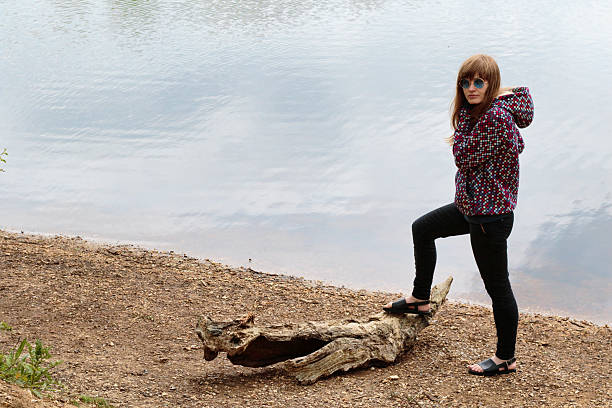 latvian outdoor girl conquers driftwood crocodile - whiteway latvian outdoor girl stock photos and pictures