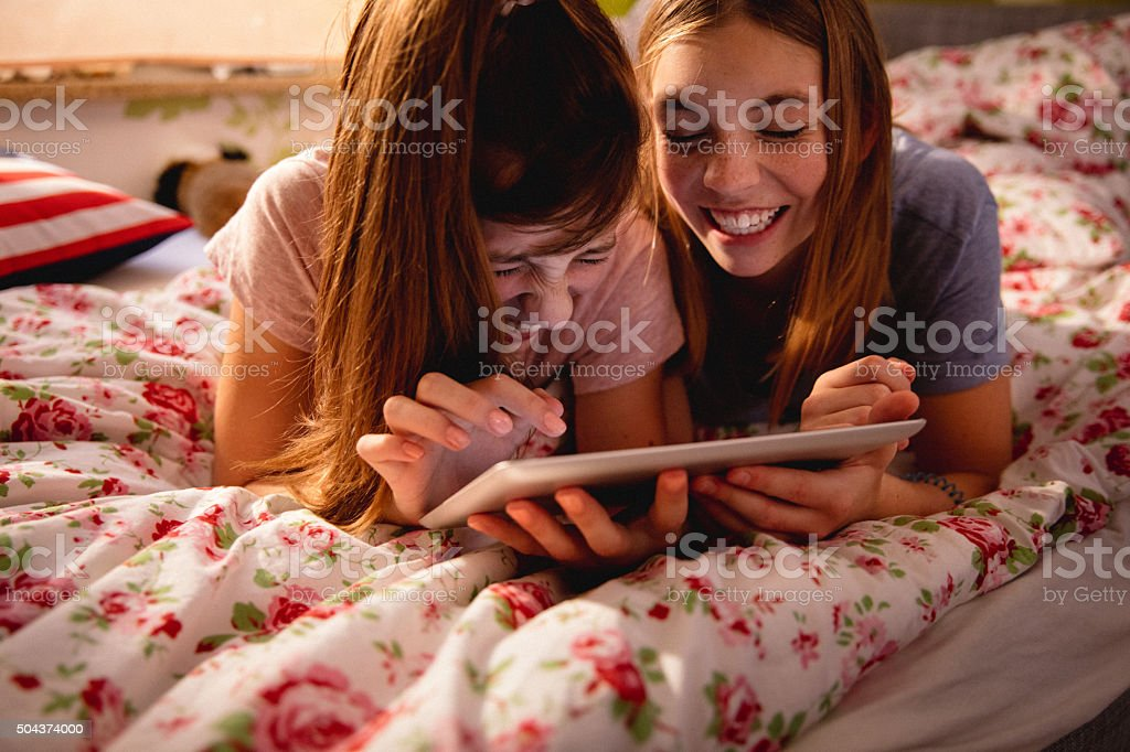 Laughing adolescent girls sharing something funny on a digital tablet stock photo