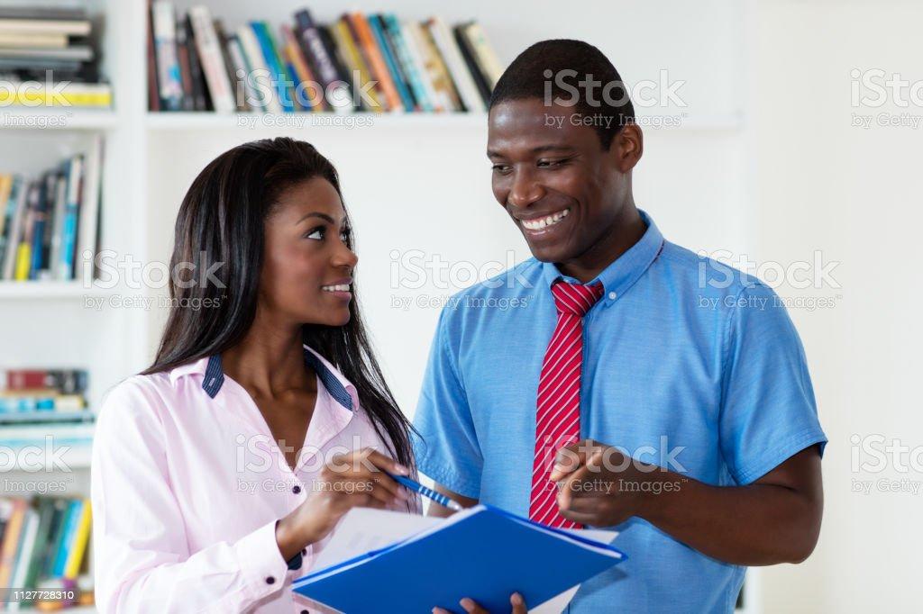 Equipo de negocios afroamericano ríe en el trabajo - foto de stock