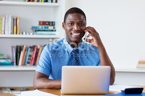 istock Laughing african american businessman with necktie at mobile phone 1087875600