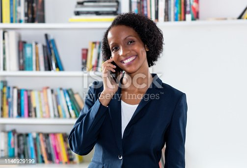 istock Laughing african american businesswoman talking with client at phone 1146929199