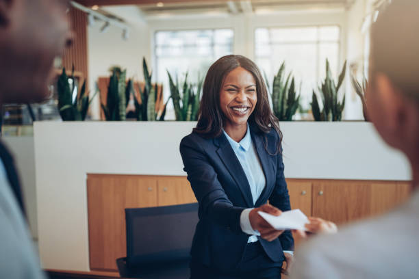 Laughing African American concierge talking with guests during check in Smiling African American concierge working behind a hotel counter giving two guests their hotel information during check in concierge stock pictures, royalty-free photos & images