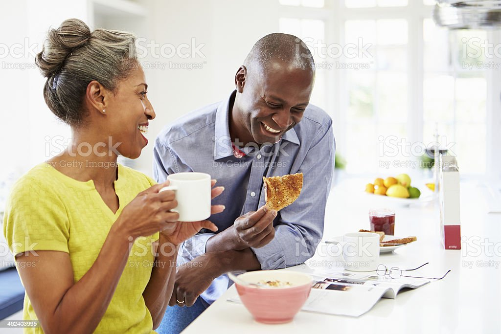 Laughing African American couple has breakfast stock photo