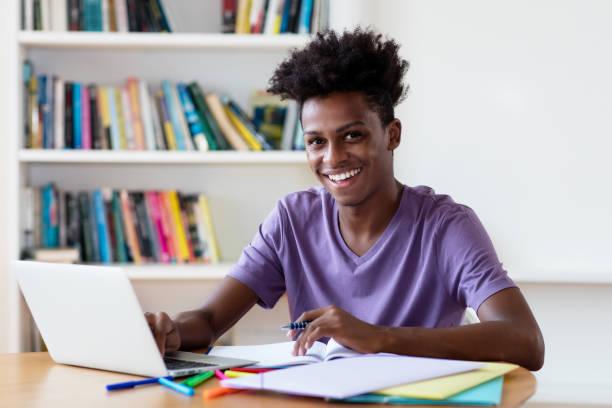 El estudiante de sexo masculino afroamericano riendo en computadora - foto de stock