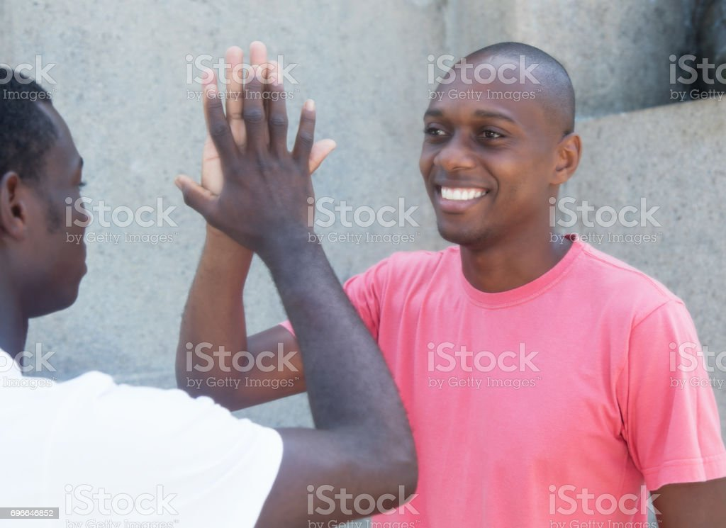 Laughing african american man giving high five stock photo