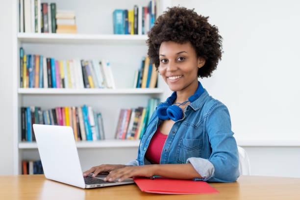 Riendo afroamericana joven adulta mujer en la computadora - foto de stock