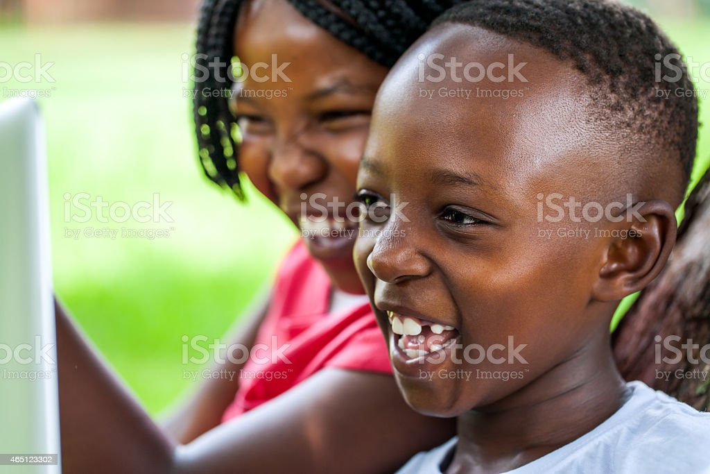 Laughing African kids looking at laptop screen. stock photo