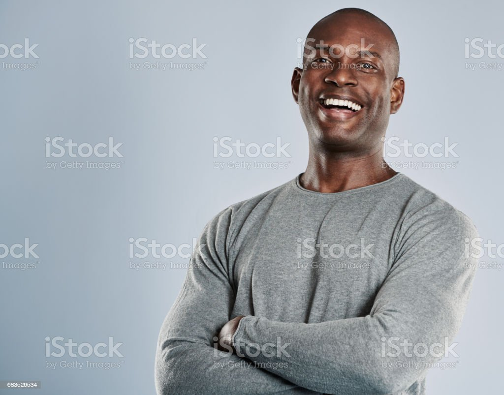 Laughing African man in gray shirt with copy space stock photo